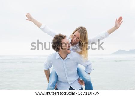 Cheerful young man piggybacking beautiful woman at the beach - stock photo