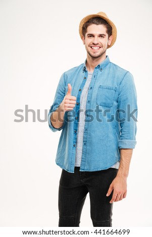 Cheerful young man showing thumbs up isolated on a white background - stock photo