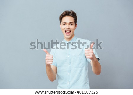 Cheerful young man showing thumbs up over gray background - stock photo