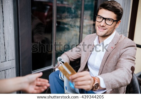 Cheerful young man sitting and paying by credit card in outdoor cafe - stock photo