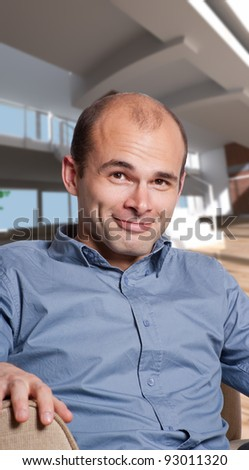 Cheerful young man sitting on a loft interior - stock photo