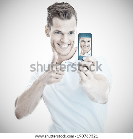 Cheerful young man taking a selfie with a modern smartphone - stock photo