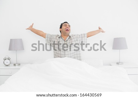 Cheerful young man waking up in bed and stretching his arms - stock photo