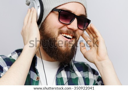 Cheerful young man, wearing on white t-shirt, gray hat, sunglasses and blue checked shirt, listening to music on headphones, on white background, in studio, close up