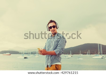 cheerful young man with a beard in sunglasses listening to music on your smartphone,posing on a pier near the sea, touchscreen, outdoor hipster portrait, close up, sea, Thailand - stock photo