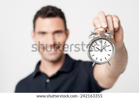 Cheerful young man with alarm clock