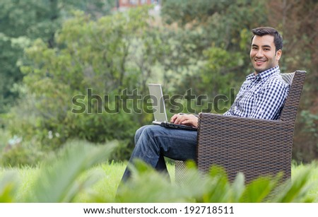 Cheerful young man with laptop, outdoor - outside. Side view sideways - stock photo