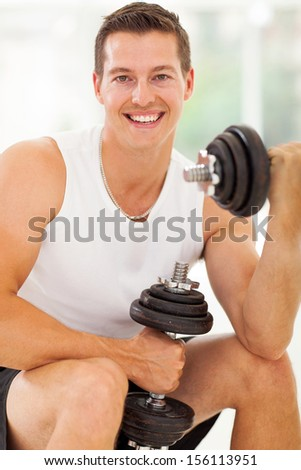 cheerful young man working out with dumbbells in gym - stock photo