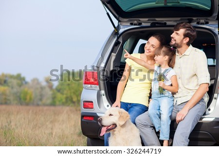 Cheerful young married couple and daughter are sitting on car trunk near dog. They are enjoying nature and smiling. The girl is pointing finger sideways. Parents are looking there with interest - stock photo