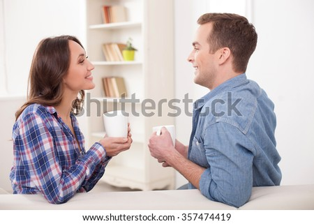Cheerful young married couple is drinking tea and smiling. They are sitting on sofa and talking - stock photo