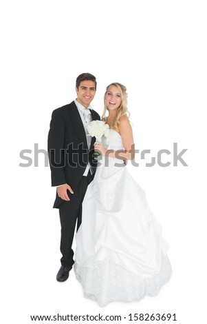 Cheerful young married couple posing smiling at camera on white background - stock photo