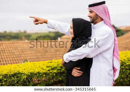 cheerful young middle eastern couple pointing outside their house - stock photo