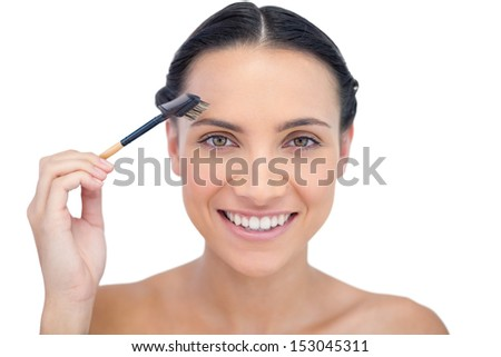 Cheerful young model using eyebrow brush on white background