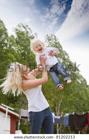 Cheerful young mother holding her baby boy up - stock photo