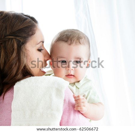Cheerful young mother taking care of her adorable baby at home - stock photo