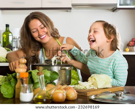 Cheerful young mother with little daughter cooking at home kitchen - stock photo
