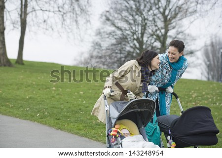 Cheerful young mothers pushing strollers in park