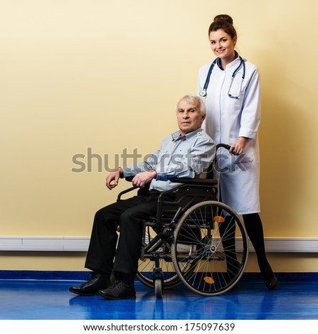 Cheerful young nurse woman with senior man in wheelchair  - stock photo