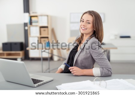 Cheerful Young Office Woman Sitting at her Desk with Laptop Computer, Smiling at the Camera. - stock photo