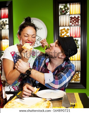 Cheerful young pair in a pizzeria.  - stock photo