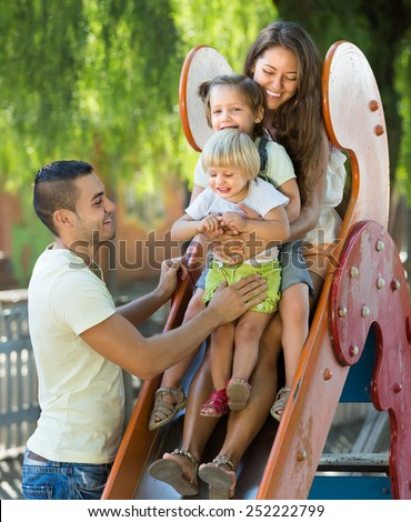Cheerful young parents with kids at children's playground in summer park  - stock photo