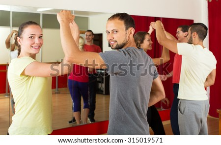 Cheerful young people dancing Latino dance in class - stock photo