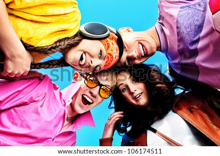 Cheerful young people laughing over blue sky. - stock photo