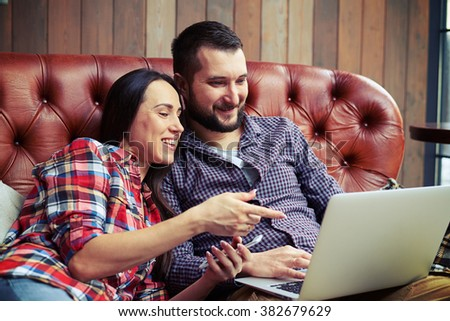 cheerful young people looking at laptop and smiling - stock photo