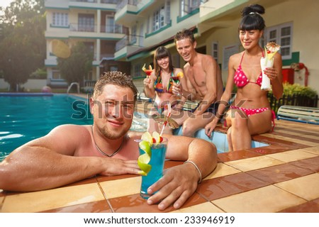 Cheerful young people sitting by swimming pool, drinking, having fun, enjoying holiday. - stock photo