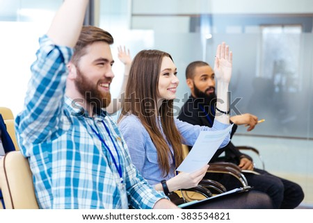 Cheerful young people sitting with raised hands and asking questions on business conference - stock photo