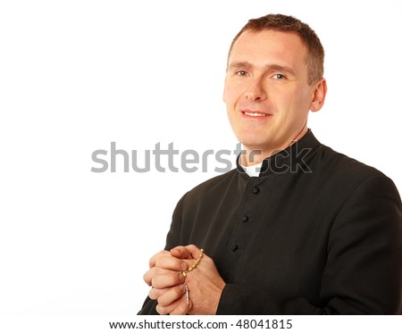 Cheerful young priest with rosary in his hands - stock photo