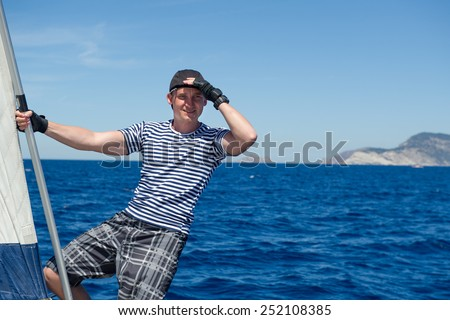 Cheerful young sailor stays at the bow of his yacht and looking to the horizon. - stock photo