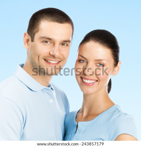 Cheerful young smiling amorous attractive couple, against blue sky background - stock photo