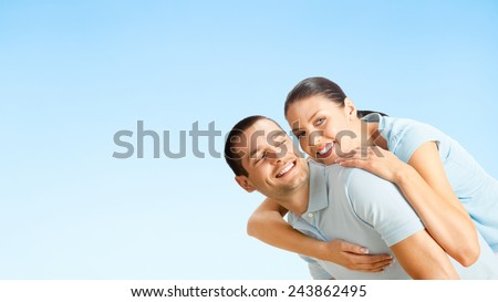 Cheerful young smiling amorous attractive couple, against blue sky background, with copy space for slogan or text