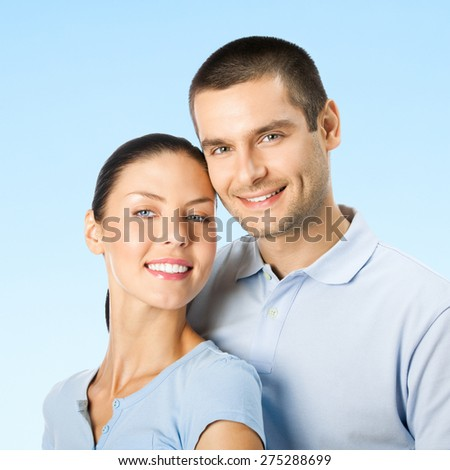 Cheerful young smiling amorous attractive couple, over blue sky background - stock photo