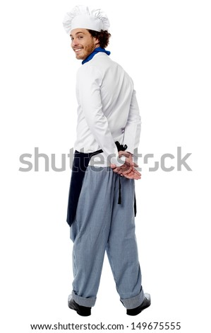 Cheerful young smiling male chef turning back - stock photo