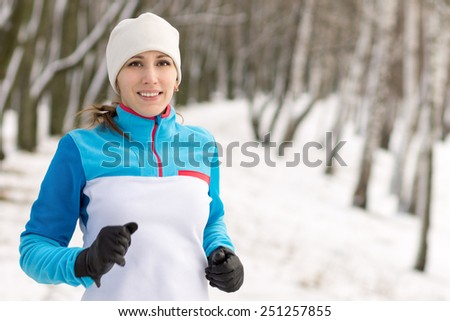 Cheerful young sport woman jogging at winter outdoor. Smiling caucasian girl running in winter park - stock photo