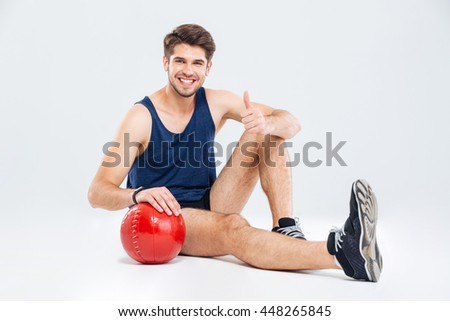 Cheerful young sportsman with red ball sitting and showing thumbs up over white background - stock photo