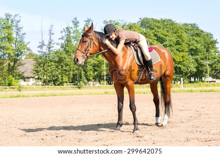 Cheerful young teenage girl equestrian riding the horseback and hugging the horse neck. Multicolored summertime outdoors image. - stock photo