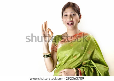 Cheerful young Traditional young Indian woman showing OK sign against a white background - stock photo
