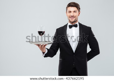 Cheerful young waiter in tuxedo standing and holding glass of red wine on tray - stock photo