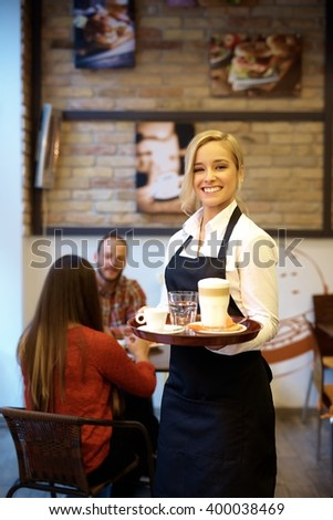 Cheerful young waitress holding tray, smiling happy, looking at camera. - stock photo