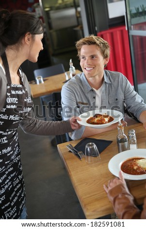 Cheerful young waitress serving dish to customers in restaurant