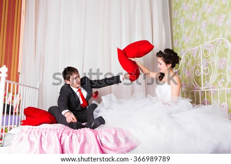 Cheerful young wedding couple pillow fighting in bed at home - stock photo