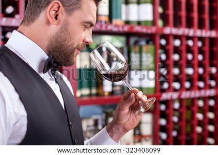 Cheerful young wine waiter is holding a glass of red wine. He is smelling it with pleasure and smiling. The man is standing in cellar. Copy space in right side