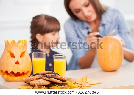 Cheerful young woman and her daughter are decorating table for Nut-Crack Night. The parent is drawing a pumpkin and smiling. The girl is looking at it with interest. Focus on cookies and juice - stock photo