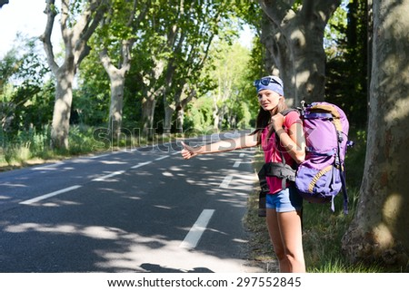 cheerful young woman backpacker hitchhiking on a roadside in summer vacation - stock photo