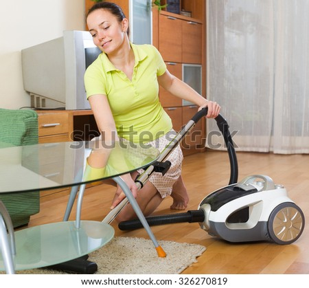 Cheerful young woman cleaning with vacuum cleaner on parquet floor at home  - stock photo