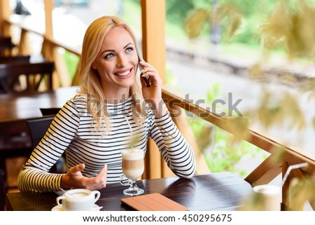 Cheerful young woman communicating on telephone - stock photo