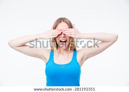 Cheerful young woman covering her eyes isolated on a white background - stock photo